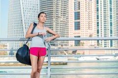 Resto antes de entrenar Mujer atlética en la ropa de deportes que lleva a cabo el bottl Foto de archivo libre de regalías