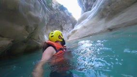 Resto attivo, giovane turista maschio felice in vestiti protettivi che galleggiano nell'acqua su fondo di tenuta delle pietre stock footage