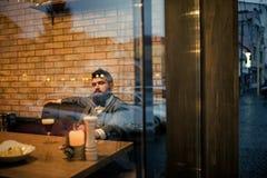 Resto barbuto dell'uomo in ristorante con il vetro di birra Tempo della birra il cliente serio della barra si siede in birra ingl immagine stock
