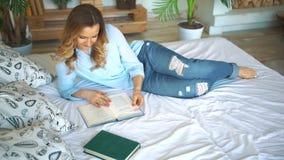 Resto, conforto, lazer e conceito dos povos - próximo acima do livro de leitura feliz da jovem mulher no quarto da cama em casa vídeos de arquivo
