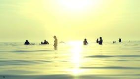 Resto de la gente en agua muy salada Siluetas de la gente que se baña en la puesta del sol almacen de video