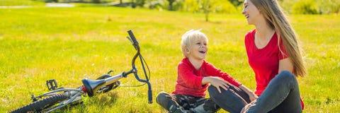 Resto de la mamá y del hijo en el césped después de montar una BANDERA de la bici, FORMATO LARGO foto de archivo libre de regalías