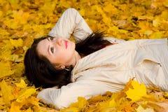 Resto de las mujeres jovenes en la hoja del otoño Fotos de archivo