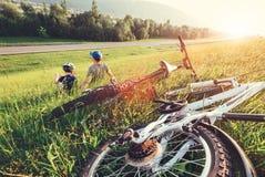 Resto del figlio e del padre insieme in alta erba verde dopo la passeggiata della bicicletta Immagine Stock