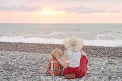 Resto del figlio e della mamma sul Pebble Beach Tempo di tramonto Vista posteriore Fotografia Stock Libera da Diritti