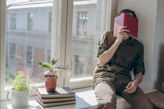 Resto del hombre joven después del libro de lectura Imagenes de archivo