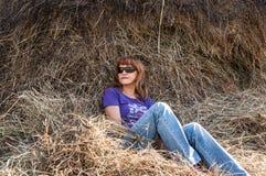 Resto del mucchio di fieno dell'erba asciutta della ragazza Immagine Stock Libera da Diritti