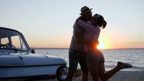 Resto del verano de pares jovenes para apuntalar el río en la puesta del sol, reunión de amantes felices en el mar del terraplén  almacen de video