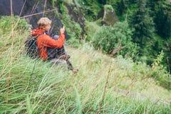 Resto del viaggiatore del giovane in alta erba verde sulla collina della montagna Immagini Stock