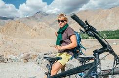 Resto del viaggiatore della bici del giovane sulla strada dell'alta montagna in Himalaya Immagine Stock