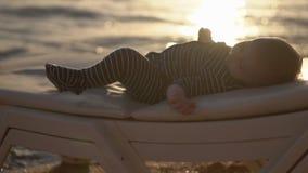 Resto do bebê no vadio no por do sol no movimento lento filme