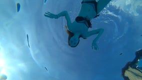 Resto do verão, menina feliz que acena sua mão sob a água e que mostra um sinal da aprovação na piscina vídeos de arquivo