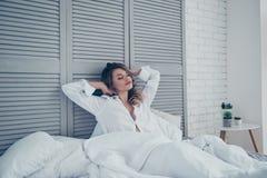 Resto, dormire, comodità e concetto della gente - allungamento della giovane donna Fotografie Stock