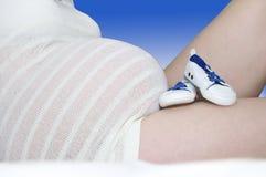 Resto dos montantes do bebê azul contra a barriga do completo-termo Imagem de Stock