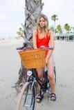 Resto godente femminile splendido dopo la guida sulla sua bicicletta classica lungo il mare Fotografia Stock