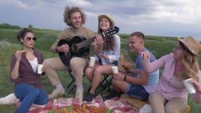 Resto in natura, amici allegri femminili e chitarra divertentesi e di gioco maschio mentre riposando sul partito di picnic su ari video d archivio