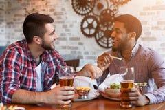 Resto nella barra Uomini che bevono birra e che mangiano le patate fritte fotografia stock libera da diritti