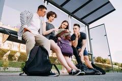 Resto stanco dei turisti alla fermata dell'autobus Immagine Stock Libera da Diritti