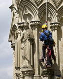 Restoration. Man suspended by a rope from the top of Salisbury Cathedral in England taking notes as to the condition of the statues and facade for restoration royalty free stock photography