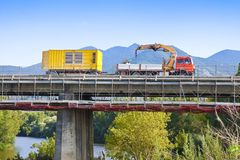 Restoration of an old damaged concrete bridge crossing a river with truck working.  royalty free stock image