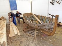 Restoration of an old wooden boat. Brest, France - July 12, 2008: Croatian traditional shipbuilders are working on the restoration of an old wooden boat during Stock Photos
