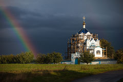 The restoration of the temple against the background of a stormy sky and rainbow. Church road sun, religion cross path danger, dome, rainbow, storm temple Stock Photo