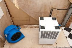 Water damage elimination. Restoration of water damage with fan and dryer royalty free stock photo