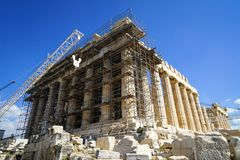 Restoration work in progress at world heritage classical Parthenon on marble block base on top of Acropolis with machine crane Royalty Free Stock Photo
