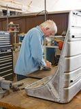Restoration Worker Buffing Aluminum for Memphis Belle Co-pilot Seat Stock Photo
