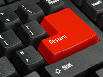 Restore key. Closeup of computer keyboard key in red color spelling Restore Stock Photos