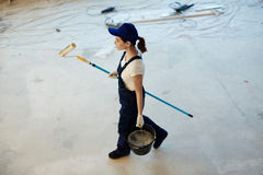 Restore worker. Young female worker carrying paintroller and bucket with water Royalty Free Stock Photo