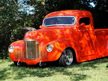 Restored Bright Orange Half Ton Low Rider Truck. Beneath trees Stock Photo