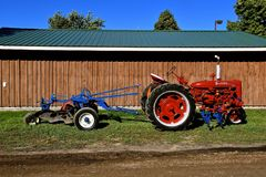 Restored Farmall C tractor pulling a blue plow. DALTON, MINNESOTA, Sept 8, 2017: A restored Farmall C tractor pulling a blue plow is displayed at the annual Stock Images