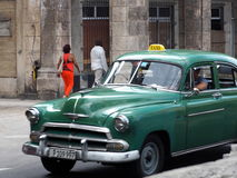 Restored Green Taxi In Havana. Restored green taxi cab driving on streets in Old Havana Royalty Free Stock Photos