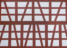 Restored half-timbered. Close-up of an exterior wall with a newly restored, brown and white half-timbered with three narrow green lines Stock Photo