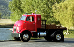 A restored historical freight truck. A red restored historical freight truck at a lush green park stock photography