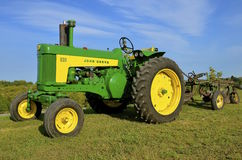 Restored John Deere 630 tractor and trip plow. ROLLAG, MINNESOTA, Sept 1: A  Restored  John Deer 630 two cylinder tractor pulling a plow is displayed at the West Stock Photo