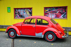 Restored Red Bug. Vintage Volkswagon Bug car mostly painted red, parked in front of yellow corrugated tin wall Stock Images