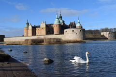 Baltic Swan Slot Kalmar Sweden. Restored Swedish renaissance castle copper roof spires white swan swimming blue water guarding Kalmar Strait royalty free stock photos