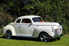 Restored White Plymouth Sedan. In front of trees Stock Photos