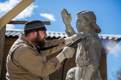 Restorer is engaged in the restoration of the statue royalty free stock photo