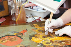 Restorer gilding on icon with agate burnisher Royalty Free Stock Images