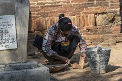 Restorative woman working, Bagan. Restorer with traditional dress working crouched, to fix a wall of a temple in Bagan. Myanmar stock photography