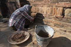 Restorative woman working, Bagan. Restorer with traditional dress working crouched, to fix a wall of a temple in Bagan. Myanmar royalty free stock images
