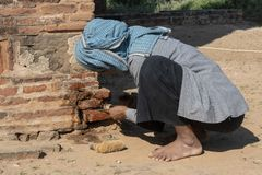 Restorative woman working, Bagan. Restorer with traditional dress working crouched, to fix a wall of a temple in Bagan. Myanmar stock photo
