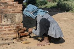 Restorative woman working, Bagan. Restorer with traditional dress working crouched, to fix a wall of a temple in Bagan. Myanmar stock photos