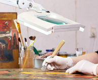 Restorer working on the ancient Christian icon Stock Photography