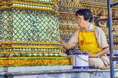Restorer working on a mosaique in Bangkok's Grand Palace Stock Photo