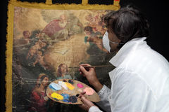 Restorer working on oil painting canvas Royalty Free Stock Image