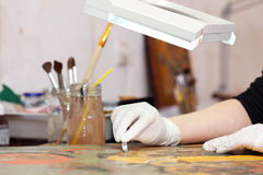 Restorer working on the old  icon Royalty Free Stock Photos